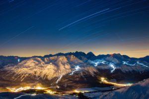 Pistenfahrzeuge präparieren das Skigebiet am Corvatsch, rechts, aufgenommen ab dem Piz Nair am 12. Dezember 2012. Langzeitbelichtung von 7159 Sekunden. Unten links die Lichter von St. Moritz, hinten das Berninamassiv.