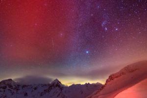 Das rote Licht am Sendeturm auf dem Piz Corvatsch färbt die umliegenden Wolken am 11. Dezember 2012. Hinten das Berninamassiv mit dem Piz Roseg, Mitte.